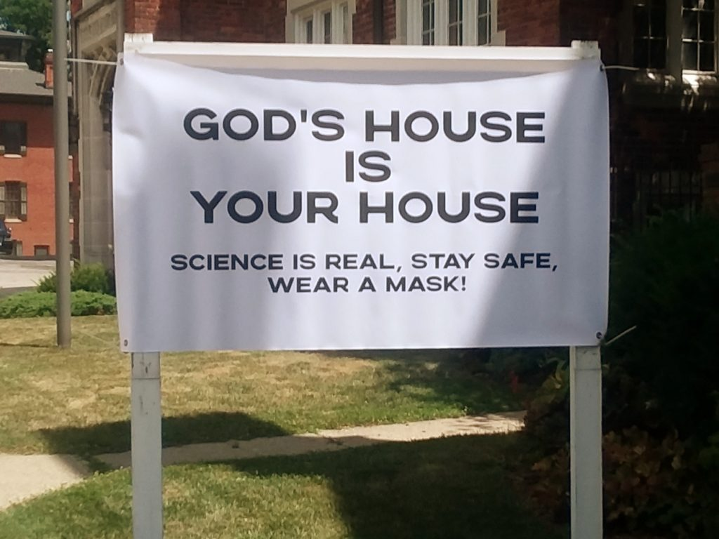 Banner outside St. Lukes that reads God's house is your house. Science is real. Stay Safe. Wear a Mask.